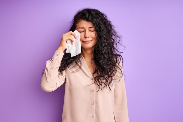 Kobieta stoi i płacze na białym tle nad fioletową ścianą, wytrzyj twarz chusteczką