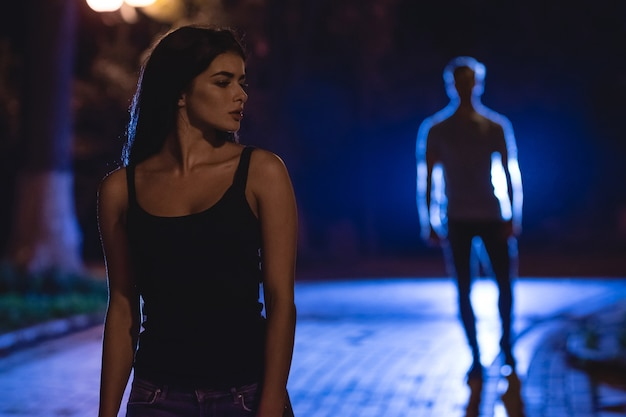 Kobieta stoi na ciemnej ulicy na tle mężczyzny. pora nocna