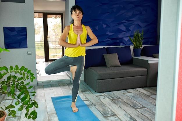 Kobieta stoi na jednej nodze i medytuje w żywym pokoju.