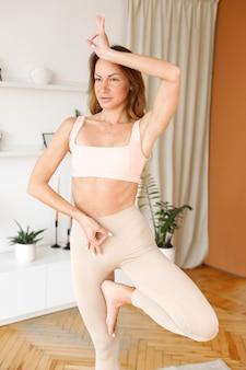 Kobieta stoi na jednej nodze jogi