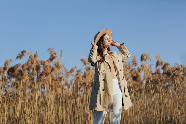 Kobieta stoi nad trzcinami i błękitnym niebem