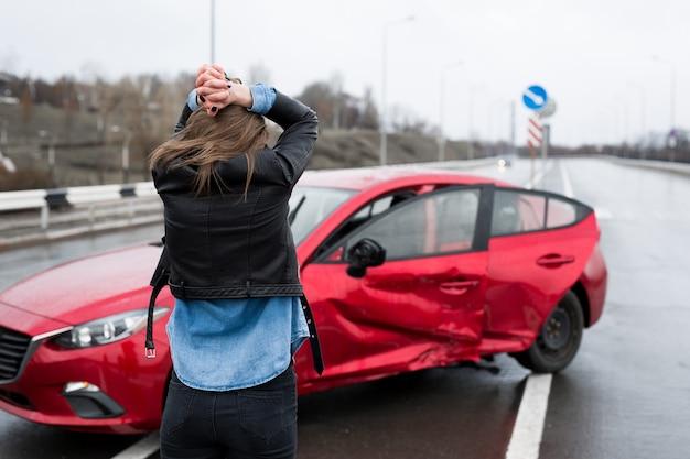 Kobieta stoi obok zepsutego samochodu po wypadku. zadzwoń po pomoc. ubezpieczenie samochodu