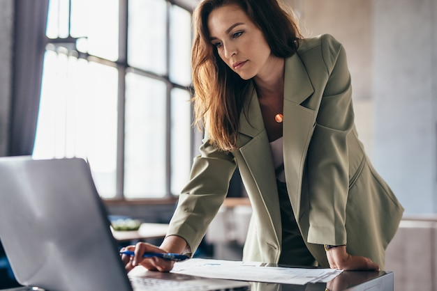 Kobieta stoi opierając się na biurku i używa swojego laptopa.