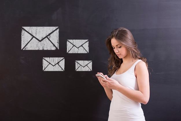 Kobieta stoi przed blackboard i pisać na maszynie wiadomością.