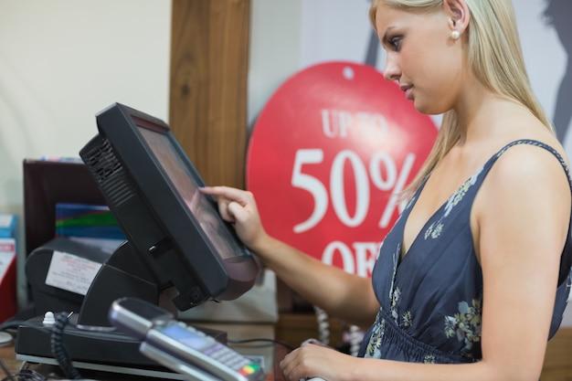 Kobieta stoi przy kasie pisania