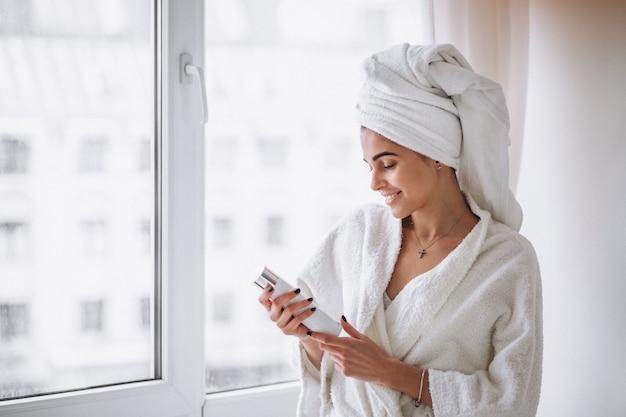 Kobieta stoi przy oknie w szlafrok