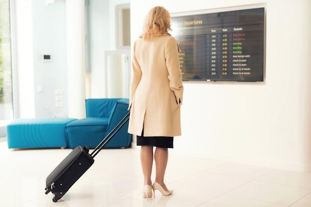 Kobieta stoi przy rozkładzie lotów na lotnisku.