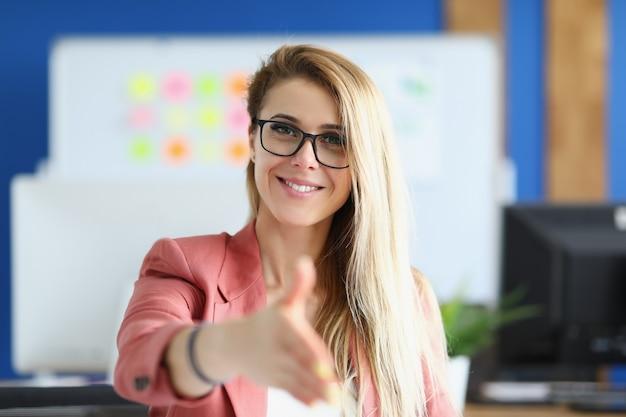 Kobieta stoi uśmiechnięta i przyjaźnie wyciąga rękę. pomyślna koncepcja układu biznesowego