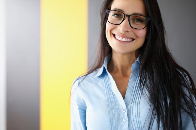Kobieta stoi w biurze i uśmiecha się zbliżenie.