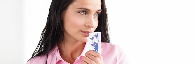 Kobieta stoi w biurze i wkłada kartę bankową do ust