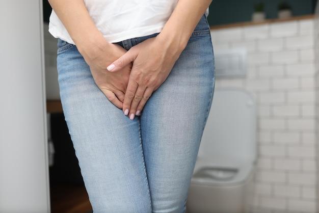 Kobieta Stoi W łazience I Zakrywa Dłonią Podbrzusze Premium Zdjęcia