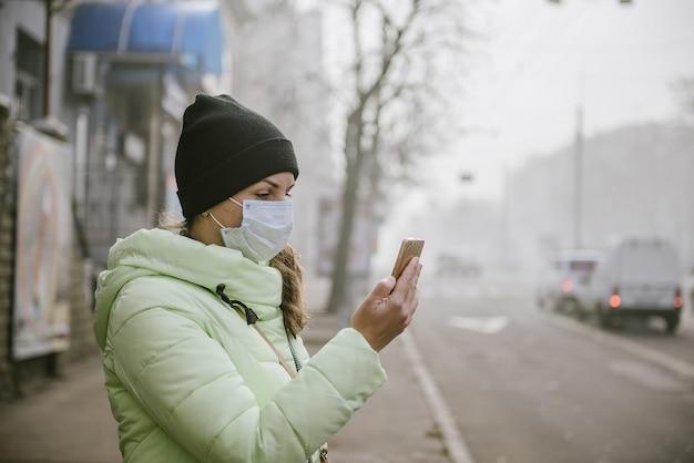 Kobieta stoi w pobliżu drogi w mieście w ochronnej masce medycznej. ochrona przed wirusami w mieście.