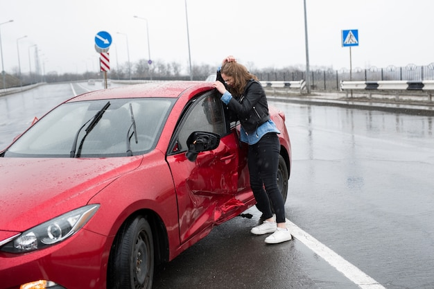 Kobieta stoi w pobliżu zepsutego samochodu po wypadku wezwać pomoc ubezpieczenie samochodu