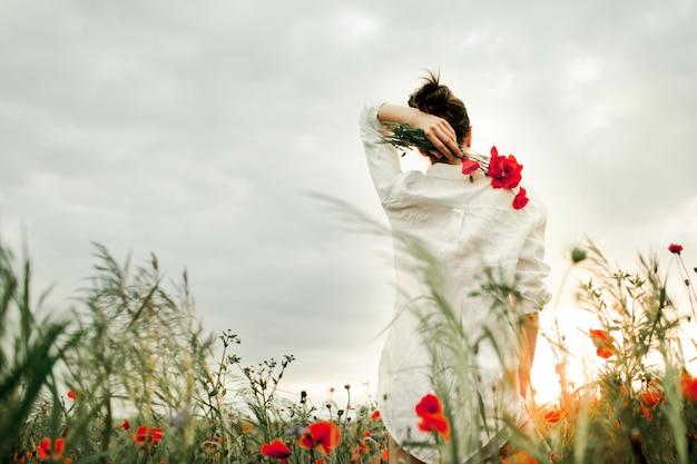 Kobieta stoi z bukietem kwiatów maku na plecach, wśród łąki