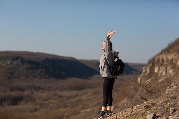 Kobieta stoi z podniesionymi rękami w górach