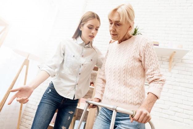 Kobieta stoi z pomocą piechura. dziewczyna jest blisko, pomaga