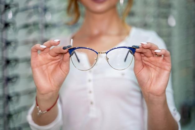 Kobieta stoi z wieloma okularami w tle w sklepie optycznym. stań z okularami. korekcja wzroku. kobieta trzyma w rękach okulary. zbliżenie.