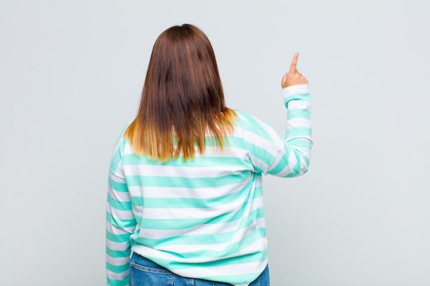 Kobieta stojąc i wskazując na obiekt