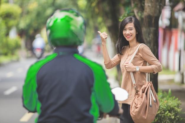 Kobieta stojąc na chodniku zamawiania motocykla taksówką