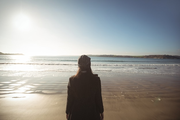 Kobieta stojąc na plaży w ciągu dnia