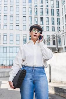 Kobieta stojąc przed dużym budynkiem