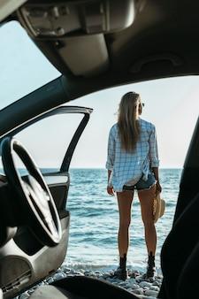 Kobieta stojąc samochodem na plaży