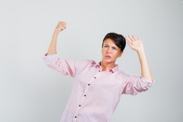 Kobieta stojąca, by bronić się w różowej koszuli i wyglądająca na zmartwioną. przedni widok.