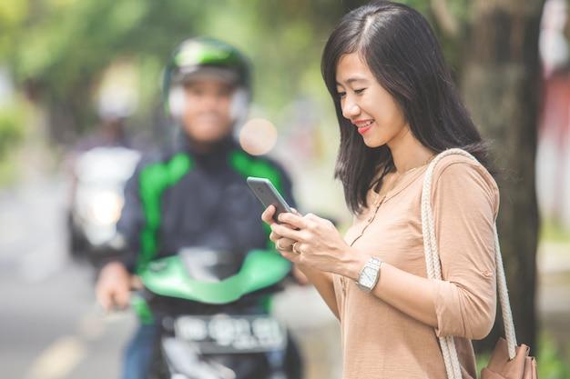 Kobieta stojąca na chodniku, zamawianie taksówki motocykl komercyjnych