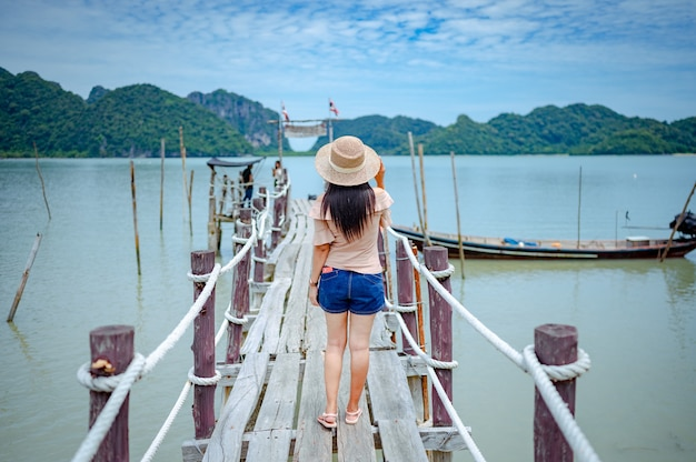 Kobieta stojąca na drewnianym moście molo w zatoce talet, khanom, nakhon si thammarat, tajlandia