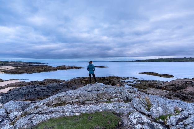 Kobieta stojąca na kamieniach na plaży koralowej w galway irlandia