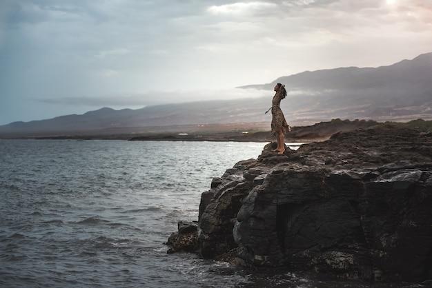 Kobieta stojąca na klifie, a poniżej oceanu