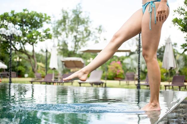 Kobieta, stojąca na krawędzi basenu i dotykając wody