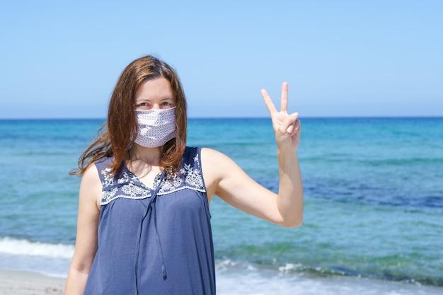 Kobieta stojąca na piasku na plaży ze zwycięskimi palcami i maską na pandemię korowirusa covid-19