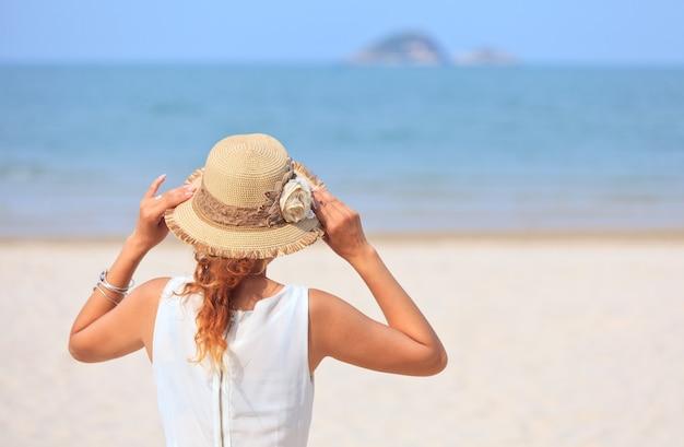 Kobieta stojąca na plaży i patrząca na morze