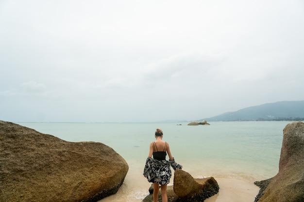 Kobieta stojąca na plaży ze skałami