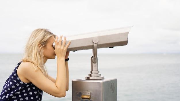 Kobieta stojąca na pokładzie liniowca wycieczkowego i patrząca przez lornetkę, pół ciała, czas trałowania