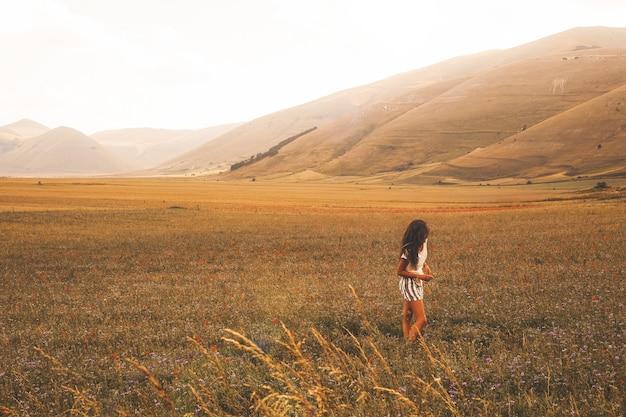 Kobieta stojąca na polu brązowej trawy