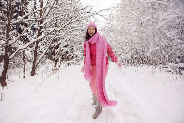 Kobieta stojąca na ścieżce w lesie w różowych ubraniach kurtka, szalik z dzianiny i czapka stoi zimą w zaśnieżonym lesie