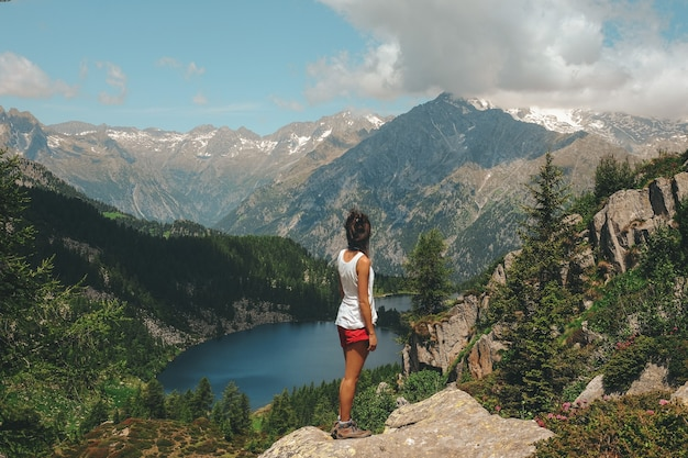 Kobieta stojąca na skale na szczycie góry