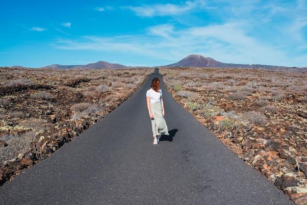 Kobieta stojąca na środku bezludnej drogi w słoneczny dzień.