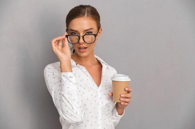 Kobieta stojąca na szarym tle ściany picia kawy w okularach.