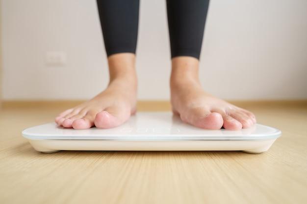 Kobieta stojąca na wagach elektronicznych do sprawdzania wagi. koncepcja diety w celu zmniejszenia brzucha