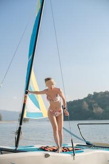 Kobieta stojąca na żaglówkach. jacht żaglowy, regaty. styl życia sportów wodnych. lato.