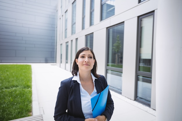 Kobieta stojąca na zewnątrz budynku biurowego