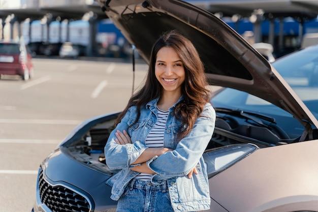 Kobieta stojąca obok zepsutego samochodu