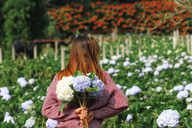 Kobieta stojąca odwróć się do ogrodu kwiaty hortensji