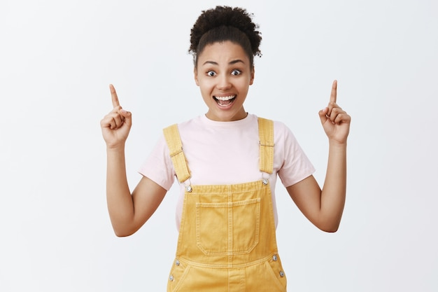 Kobieta stojąca pod wrażeniem i zdumiona w uroczym żółtym kombinezonie, wskazująca w górę z uniesionymi palcami wskazującymi