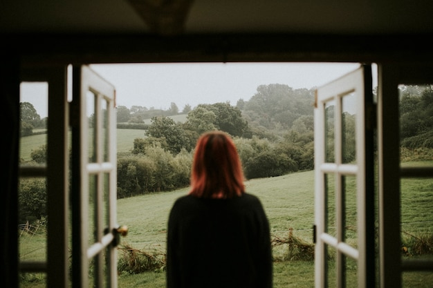 Kobieta stojąca przed domem