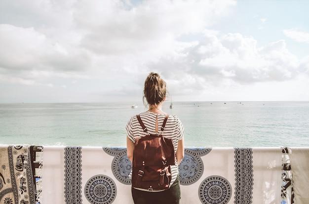 Kobieta stojąca przed zbiornikiem wodnym w ciągu dnia