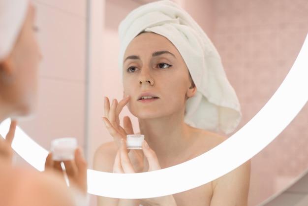 Kobieta stojąca przy lustrze w łazience i nakładająca krem nawilżający na twarz. selektywne skupienie